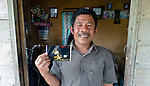 In 2014, Nurul Huda holds a photo of him fishing at night in 2007 off the Indonesian island of Nias. Huda, a resident of the seaside village of Olora, survived a giant March 2005 earthquake on Nias, yet lost much of his fishing equipment. Church World Service, a member of the ACT Alliance, provided new nets and boats for the fishers of Olora, allowing them to restart their lives. Yet fish have grown scarce in recent years, while fuel prices have risen, making it harder for fishers to earn a living. Huda no longer can afford a motor, and so fishes closer to the island, where the fish are smaller. Climate change has also made it more difficult to predict fish movements, and changing weather patterns can surprise the fishermen at sea. Huda, not surprisingly, wonders if his 16-year old son should pursue another line of work.