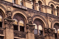architectural detail gargoyles arched windows, early victorian style commercial building.