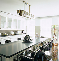 A chrome light designed by Thierry Despont is suspended above the long contemporary dining table in the centre of the kitchen