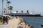 A family rides a pedal surrey along the Shoreline Marina Breakwater across from the Queen Mary in Long Beach, CA
