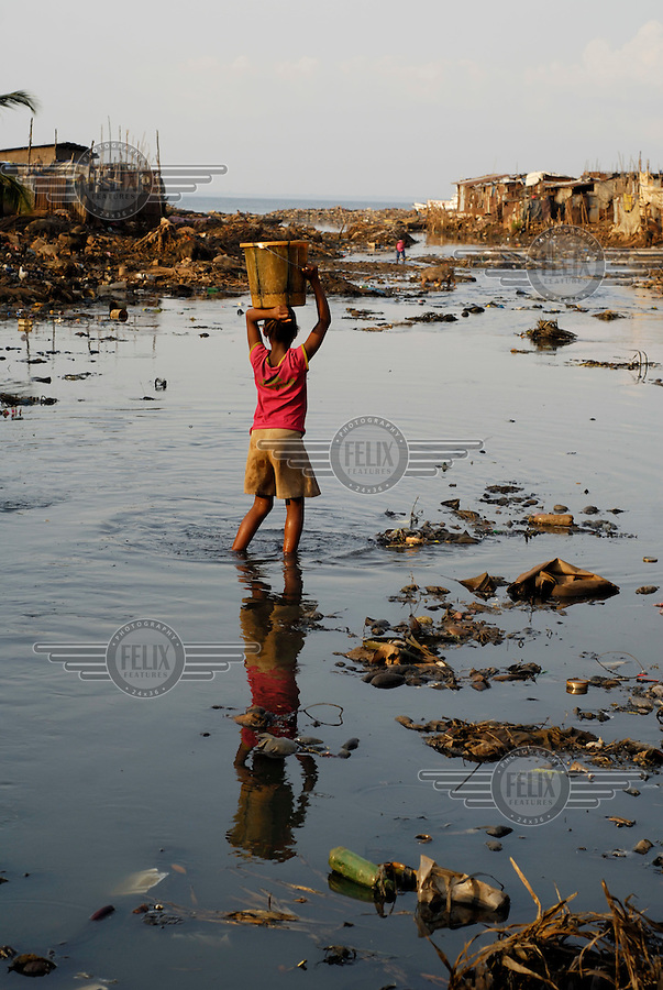 Kroo Bay, Freetown, Sierra Leone...Story on child and maternal health in the Kroo Bay slum community in Freetown, Sierra Leone, which has the World's worst infant and maternal mortalitly rates. One in 4 children die before they reach the age of 5 and one in 6 mothers dies during child birth (in the UK, the rate is one in 3,800)...The Kroo Bay Community Health Centre has a catchment area of over 8,000 people but lacks adequate facilites to provide even basic care. The clinic lacks even the basics, such as bedpans, surgical spirits and cotton wool. It has no electricity and clean drinking water must be fetched from the nearby well everyday...A child carrying a water container wades through the river, which is choked with rubbish and used by many to defecate in. During the rainy season the river, clogged up by the city's rubbish which flows downstream, often floods and the stagnant water become a breading ground for disease and malarial mosquitos...© 2007 Aubrey Wade. All rights reserved.