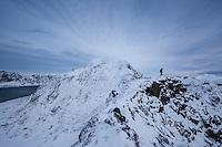 Hiker descenting wintry ridge from summit of Mannen mountain peak, Vestvågøy, Lofoten Islands, Norway