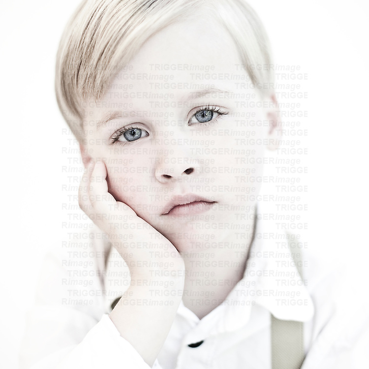 Male child with blonde hair and blue eyes wearing white shirt and braces resting head in hand looking bored at camera