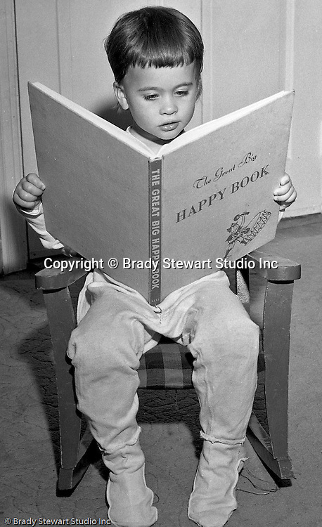 """Pleasant Hills PA:  Brady Stewart Studio participated in a national promotion for American Hardware Catalog Cover - 1950.  The contest asked for submissions to include a child reading a book at night time.  In this image, Cathleen Brady Stewart is reading the """"The Great Big Happy Book""""."""