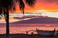An outrigger canoe at rest on a Maui beach as the sun sets behind Lana'i.