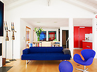 The living area has been designed so that contrasting bright colours have been used to designate different purposes for the large room, such as the blue furniture in the living area, and the red cupboards in the kitchen