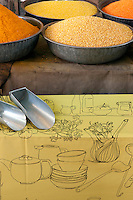 Spices and pulses are sold in metal bowls from a stall in the market