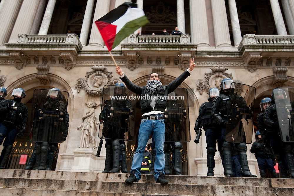 A man stands waving a Palestinian flag in front of a cordon of riot police blocking access to the Palais Garnier opera house in Paris, France, 17 October 2009, during a protest by several thousand people against Israel's military offensive in the Palestinian Gaza Strip.