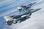 Two F-16C's from Hill Air Force Base fly tight formation during a shallow banking turn. Noticeable on the nearest pylon is a long dart-like probe called the Nellis Air Combat Training System (NACTS). The NACTS pod can track up to 100 individual aircraft denoting their altitude, air speed, range positioning and more for a complete assessment of actions to be reviewed in detail at the mass debrief following the mission.