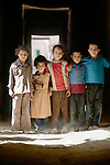 Children standing in a pool of light shining in from a door in a long dark hallway, Morocco