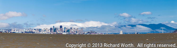 The San Francisco city skyline and part of the Bay Bridge as seen from across San Francisco Bay at Shoreline Park in Alameda, California.
