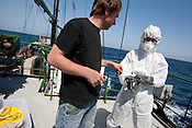 Daisuke Miyachi of Greenpeace Japan demonstrates wearing nuclear radiation protection clothing suits on board the Greenpeace ship Rainbow Warrior, as it transits northwards to Fukushima, Japan, on Monday 25th April 2011.
