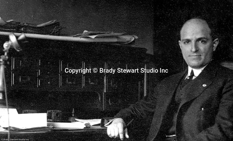 Pittsburgh PA:  Brady Stewart sitting at his desk at B.W. Stewart Studio - 1912.  Brady Stewart started his photography business after returning from a stint of homesteading in Idaho with three friends from Pittsburgh.  During this time, if you were the sole owner of a business, you used your first two initials and last name.