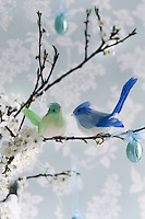 Detail of a pair of decorative birds sitting on a cherry blossom branch in an Easter still-life