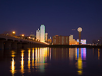 The Dallas, Texas skyline at night reflected in the flooded Trinity River.