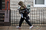 A woman carries two children as Hurricane Sandy begins to affect the area in Jersey City, United States. 29/10/2012. Photo by Kena Betancur/VIEWpress.