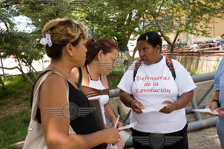 "Margarita Gumez (right) distributes leaflets and talks with women about security and protection measures and the new ""Organic Law for the right of women to a life free of violence"" in the La Vega neighbourhood of Caracas."