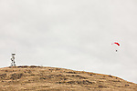 One adult male lifts off from the side of Steptoe Butte near a radio and microwave antenna tower.