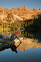 ID00339-00...IDAHO - Backpacker dipping a pan into Alpine Lake in the early morning in the Sawtooth Wilderness Area.