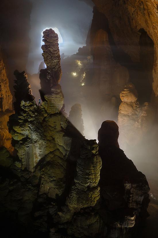 A caver is dwarfed by massive stalagmites in Hang Son Doong. Hang Son Doong is located in Phong Nha Ke Bang National Park, Vietnam.