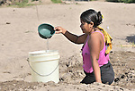 A woman obtains water by digging into a riverbed near Santa Paula, a hot and isolated village in northwestern Nicaragua.