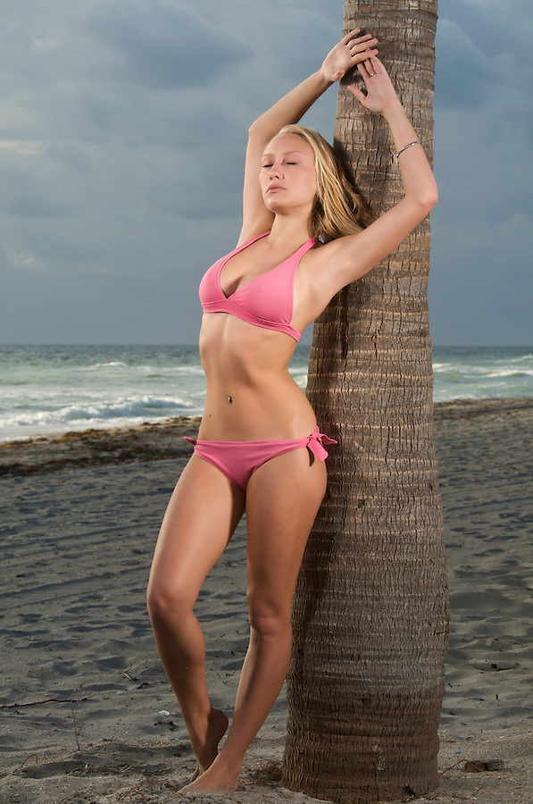 A young caucasian women relaxes in the beach in a stormy morning.