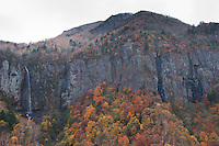The Fudou Taki Waterfall falls over high grey cliffs in stark contrast to the autumn scenery in the mountains around Nagano, Japan.