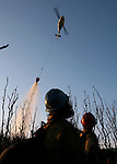 U.S. Forest Service firefighters Dave Noxon, left, 44, and captain Adam Leyba, 32, both from American River Hot Shots, watch a helicopter make a water drop on the Esperanza Fire southeast of Poppet Flats on Sunday, October 29, 2006. The hot shots work in tandem with the helicopter. Once the helicopter makes water drops to control the flames, the hot shots seek out hot spots and extinguish them on the ground during the fourth day of the Esperanza fire. The fire claimed the lives of five firefighters last Thursday.