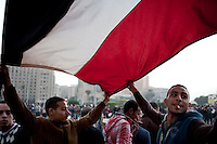 Protesters carrying an Egyptian flag in Tahrir Square. Continued anti-government protests take place in Cairo calling for President Mubarak to stand down. After dissolving the government, Mubarak still refuses to step down from power.