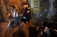 Cyclist at night-the bicycle is often in close contact with India's holy street roaming cows.