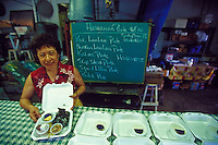 Auntie holding the Ono Nui Hawaiian plate lunch special with laulau in their Kaneohe restauant on Oahu