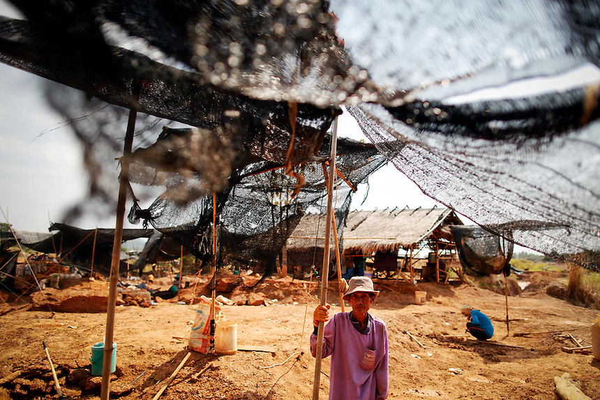 A man holds a netting as people work at a primitive gold mine in Panompa near Phichin February 17, 2011. A group of Thais use primitive tools and methods to extract gold from self-run mines near the countries biggest and most modern Chatree gold mine. A family working at the mine can get around one gram of gold per day they sell at the site for about 1000 Thai bahts (32 USD).   REUTERS/Damir Sagolj (THAILAND)