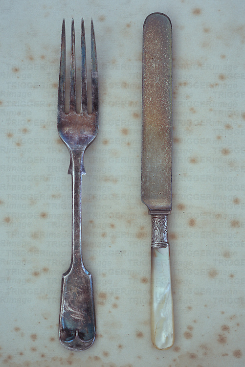 Antique silver table fork lying next to knife with mother-of-pearl handle on antique paper