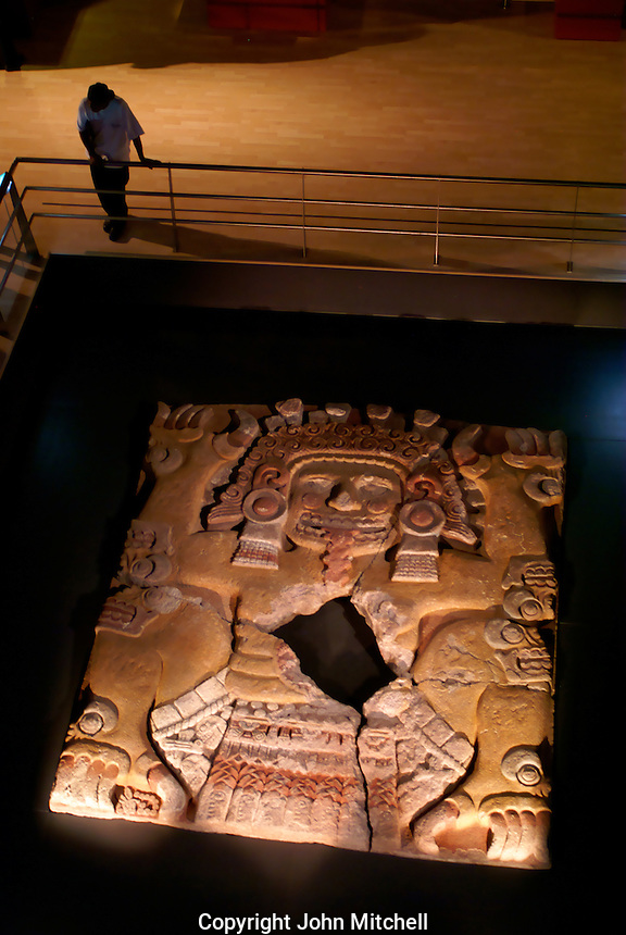 Man looking at the Tlaltecuhtli sculpture in the Templo Mayor Musem, Mexico City. This sculpture was discovered in 2006 in downtown Mexico City. It is the largest Aztec artifact found so far.