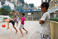 A kid watches his friends play football at a small pitch in Favela Santo Amaro in the hills around Rio de Janeiro