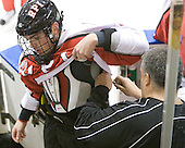 Dana McGuane (RPI - Equipment Manager) quickly stitches a repair to Tyler Helfrich's (RPI - 15) equipment. - The visiting Rensselaer Polytechnic Institute Engineers tied their host, the Northeastern University Huskies, 2-2 (OT) on Friday, October 15, 2010, at Matthews Arena in Boston, MA.