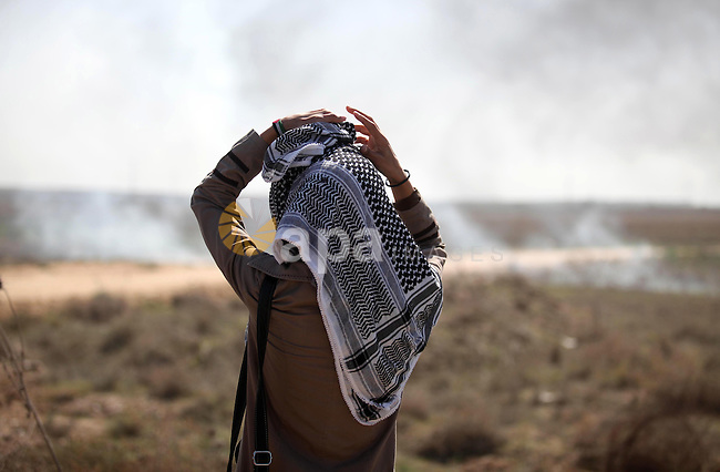 "A female Palestinian protester looks on during clashes with Israeli security forces near the border fence between Israel and the Gaza Strip on October 11, 2015, east of Gaza City. An Israeli air strike in Gaza killed a pregnant woman and her toddler and Hamas warned the Jewish state against ""foolishness"" as Palestinian unrest spun further toward a full-scale uprising. Photo by Ashraf Amra"