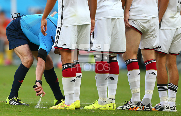 Referee Milorad Mazic uses vanishing spray to mark where the Germany wall must stand for a Portugal free kick