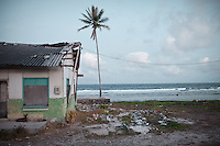 A tumb in front of a house in Annibare. A young boy was buried there, after drowning in a water tank. Land is restricted in Nauru, due to extensive mining inland. Cemetery are full, so some Nauruans have been allowed to bury their family member in front of their house...Nauru, officially the Republic of Nauru is an island nation in Micronesia in the South Pacific.  Nauru was declared independent in 1968 and it is the world's smallest independent republic, covering just 21square kilometers..Nauru is a phosphate rock island and its economy depends almost entirely on the phosphate deposits that originate from the droppings of sea birds. Following its exploitation it briefly boasted the highest per-capita income enjoyed by any sovereign state in the world during the late 1960s and early 1970s..In the 1990s, when the phosphate reserves were partly exhausted the government resorted to unusual measures. Nauru briefly became a tax haven and illegal money laundering centre. From 2001 to 2008, it accepted aid from the Australian government in exchange for housing a Nauru detention centre, with refugees from various countries including Afghanistan and Iraq..Most necessities are imported on the island..Nauru has parliamentary system of government. It had 17 changes of administration between 1989 and 2003. In December 2007, former weight lifting medallist Marcus Stephen became the President.