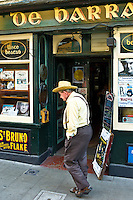 Man walking past de Barra bar in Timoleague, West Cork, Ireland