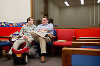 Jason Holling, left, and Justin Karas, right, sit in the waiting room for adoptive families to take Abby to stand before a judge on September 3, 2014 at the Richard J. Daley Center in Chicago, Illinois.