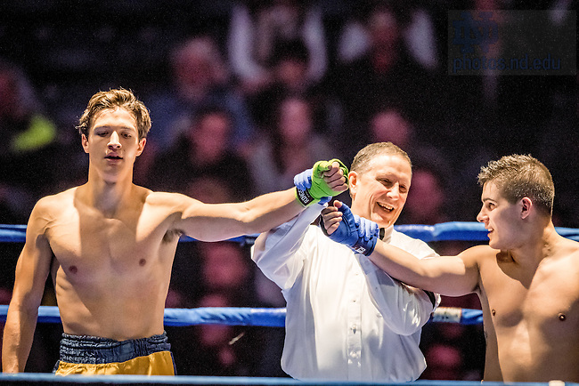 """March 3, 2017; Greg Arts (gold trunks) and Garrett """"FedEx"""" Schmelling (blue trunks) stand for the announcement of the winner in their 159lb. division bout. Arts won in a split decision. (Photo by Matt Cashore/University of Notre Dame)"""