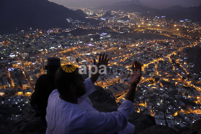 Muslim pilgrims pray on their way up Noor Mountain in the holy city of Mecca before the start of the annual Hhjj pilgrimage, on November 23, 2009. Some 2.5 million Muslims from more than 160 countries converge annually on the Islamic holy cities of Mecca and Medina in western Saudi Arabia. Photo by Ashraf Amra