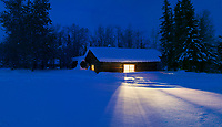 Yellow light spilling out of a log cabin window on the snow in Wiseman, Alaska,