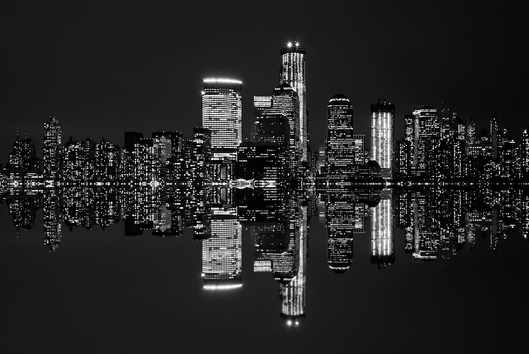 Black and white image of New York City's skyline at night.