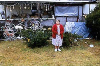New York, Plattsburg, Keenseville. Woman at home in front of her trailer.