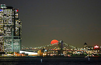 JERSEY CITY, NJ - OCTOBER 17: The moon rises behind the Brooklyn bridge in New York City on October 16, 2016 as seen from Jersey City, NJ. (Photo by Kena Betancur/VIEWPRESS)