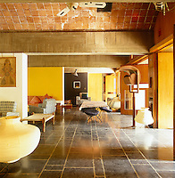 The open-plan living area has a floor of Kadappa Indian stone with doors of cedar wood and vaulted ceilings of local brick