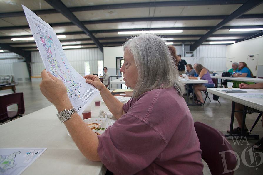 RYAN MCGEENEY/Arkansas Democrat-Gazette --06-26-2014-- Carolyn Griffith of West Fork examines a map of the seven sub-watersheds that make up the Beaver Lake Watershed during a public meeting Thursday evening at the West Fork Community Center. The meeting was one of a <br />series of public outreach meetings organized by the Beaver Watershed Alliance with the goal of learning about problems and residents' concerns in streams throughout the area.