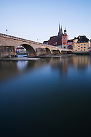 Historic 12th century stone bridge (Steinerne Brücke) crosses Danube river with Saint Peters cathedral rising in background, Regensburg, Germany